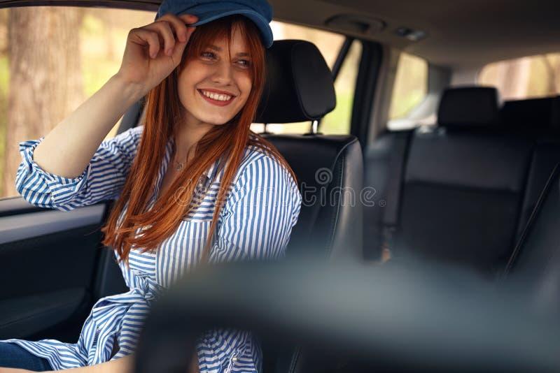 Glimlachend meisje in de auto die in wegreis en het hebben van pret genieten van royalty-vrije stock foto