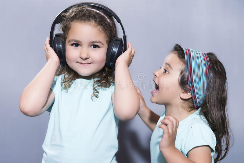 Glimlachend meisje die aan muziek in hoofdtelefoons met zuster dichtbij het gillen luisteren royalty-vrije stock afbeeldingen