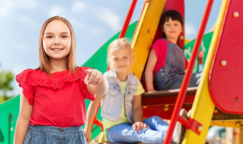 Glimlachend meisje die aan u op speelplaats richten royalty-vrije stock fotografie