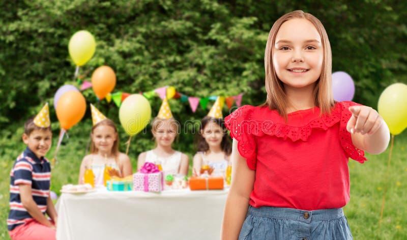 Glimlachend meisje die aan u op verjaardagspartij richten royalty-vrije stock afbeelding