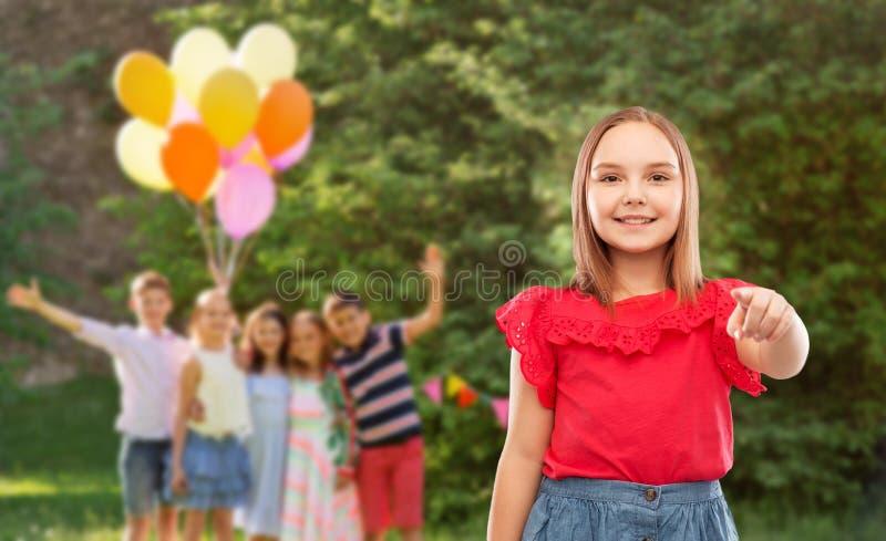 Glimlachend meisje die aan u op verjaardagspartij richten royalty-vrije stock afbeeldingen