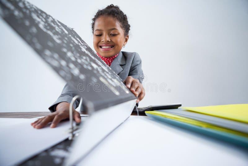 Glimlachend meisje die als onderneemster beweren die bij bureau werken stock fotografie