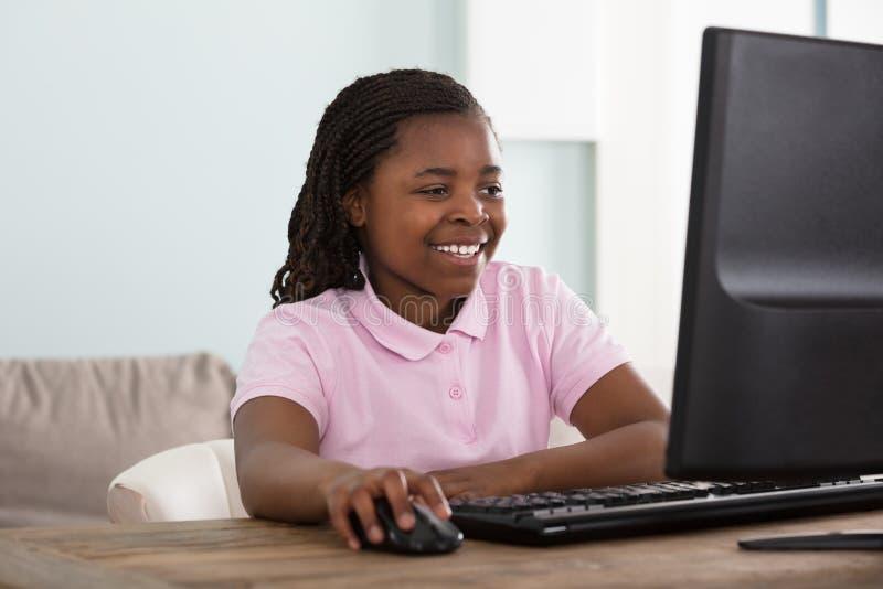 Glimlachend Meisje die Computer met behulp van stock foto
