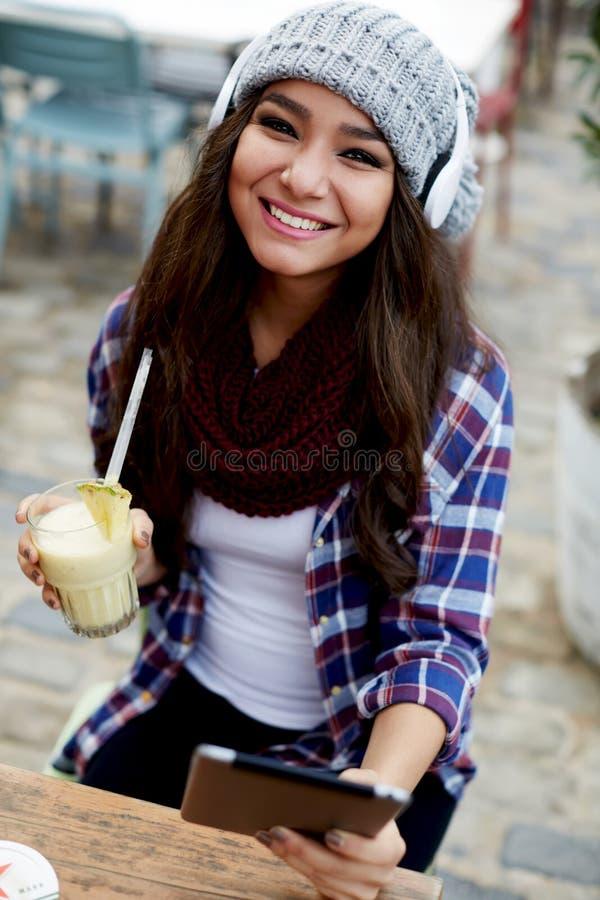 Glimlachend meisje die digitale tabletzitting in koffie gebruiken stock fotografie