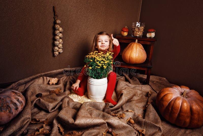 Glimlachend meisje die duim op het zitten met vaas van bloemen tonen royalty-vrije stock foto