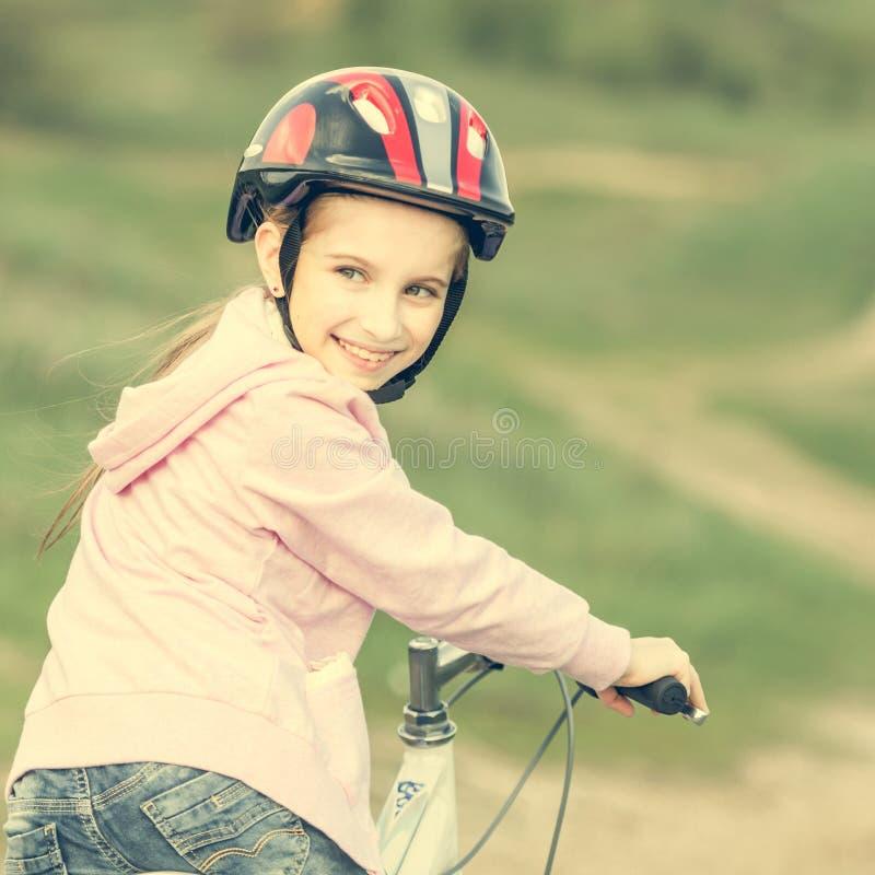 Glimlachend meisje die een afgewezen fiets berijden stock foto's