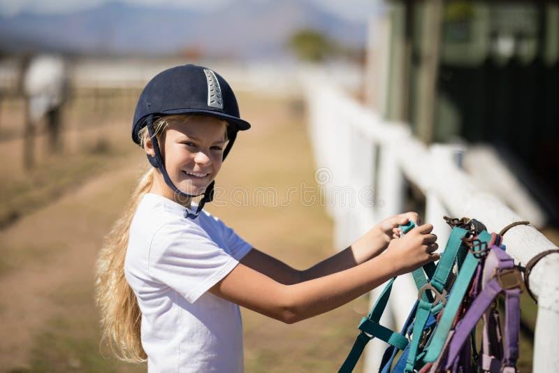 Glimlachend meisje die een paardsnuit in de boerderij opnemen stock afbeeldingen