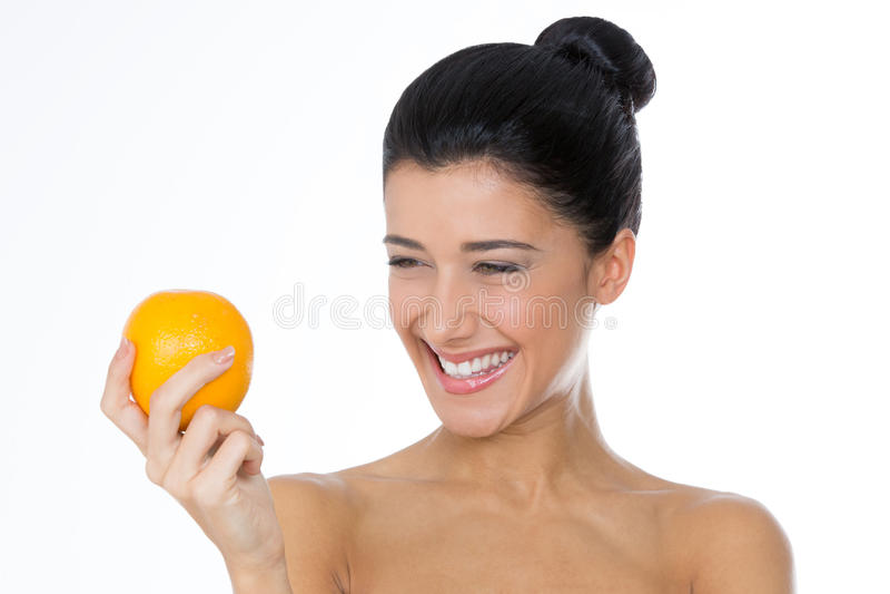 Glimlachend meisje die een sinaasappel bekijken stock fotografie