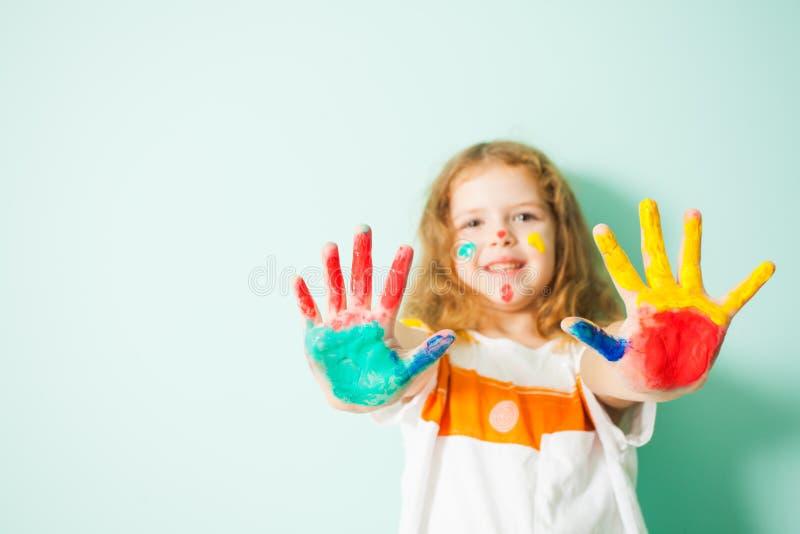 Glimlachend meisje die haar geschilderde palmen op camera tonen stock foto