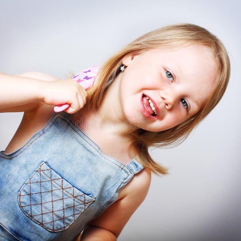 Glimlachend meisje die haar haar borstelen stock afbeelding