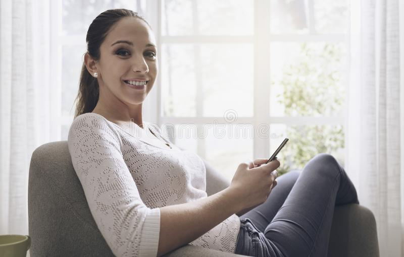 Glimlachend meisje die haar smartphone thuis gebruiken royalty-vrije stock fotografie