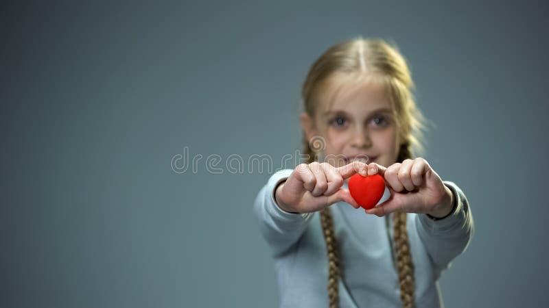 Glimlachend meisje die hartcijfer tonen in camera, liefde en vriendelijkheidsconcept royalty-vrije stock afbeeldingen