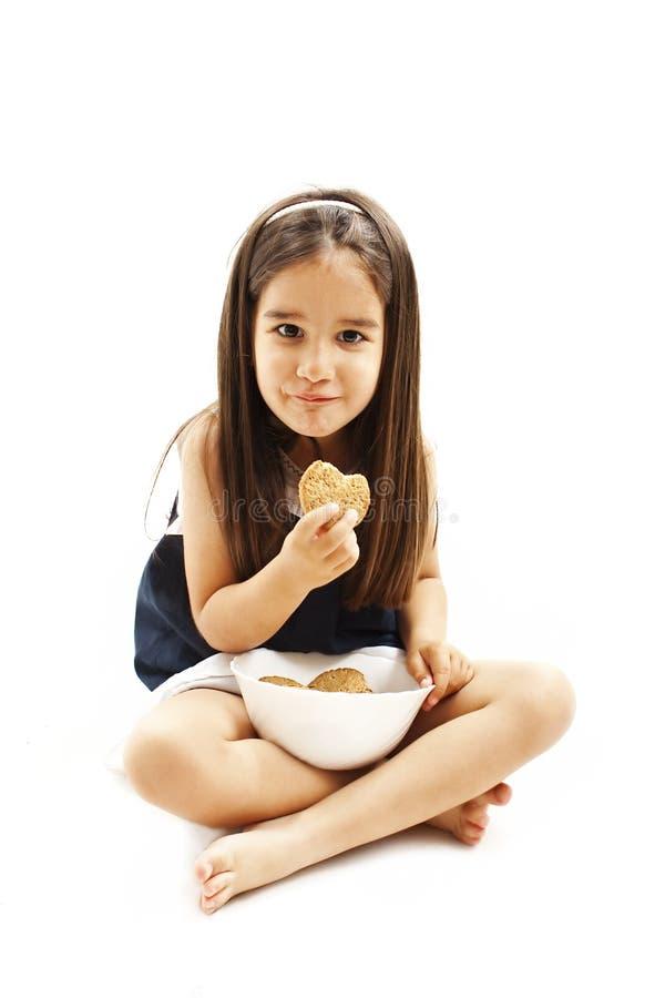 Glimlachend meisje die koekje of koekje eten royalty-vrije stock foto's