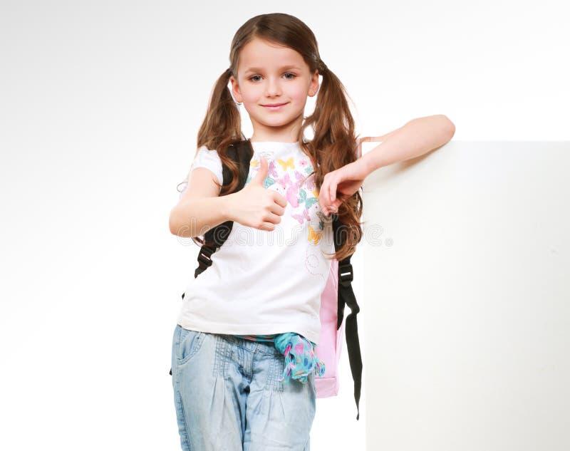 Glimlachend meisje die lege witte die banner houden - op witte achtergrond wordt geïsoleerd stock afbeeldingen