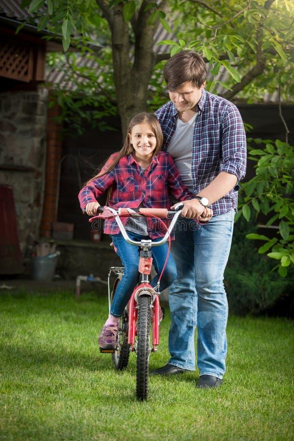 Glimlachend meisje die leren hoe te een fiets met haar vader bij p te berijden stock fotografie