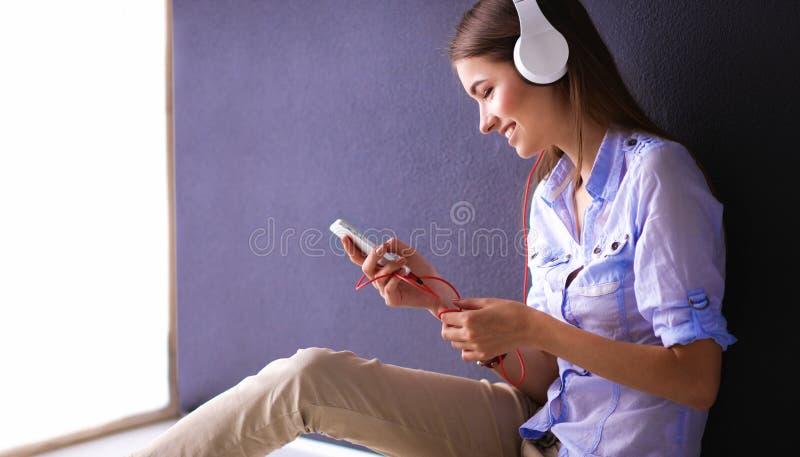 Download Glimlachend Meisje Die Met Hoofdtelefoons Op De Vloer Dichtbij Muur Zitten Stock Foto - Afbeelding bestaande uit hoofdtelefoon, telefoon: 107704898
