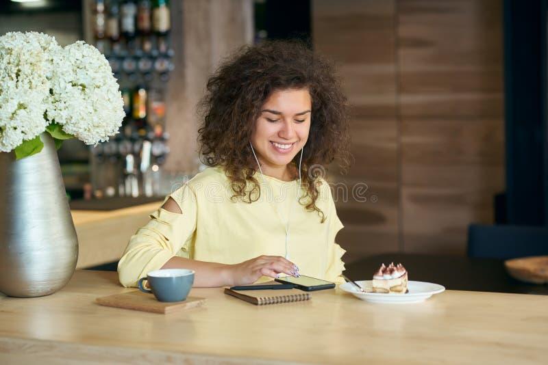 Glimlachend meisje die met krullend haar aan muziekzitting luisteren in restaurant stock afbeeldingen