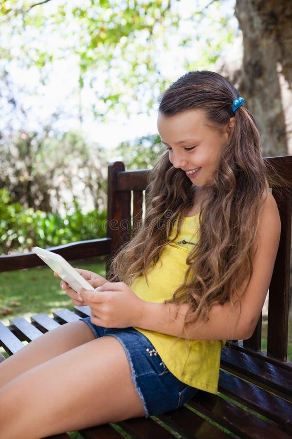 Glimlachend meisje die mobiele telefoon met behulp van terwijl het zitten op houten bank royalty-vrije stock foto