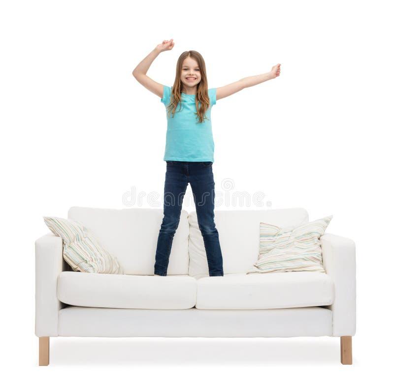 Glimlachend meisje die of op bank springen dansen stock afbeelding