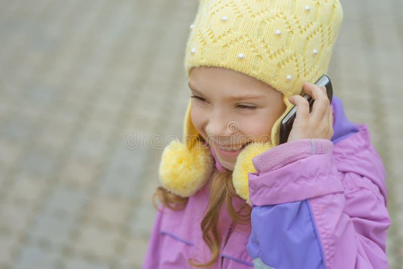 Glimlachend meisje die op telefoon spreken