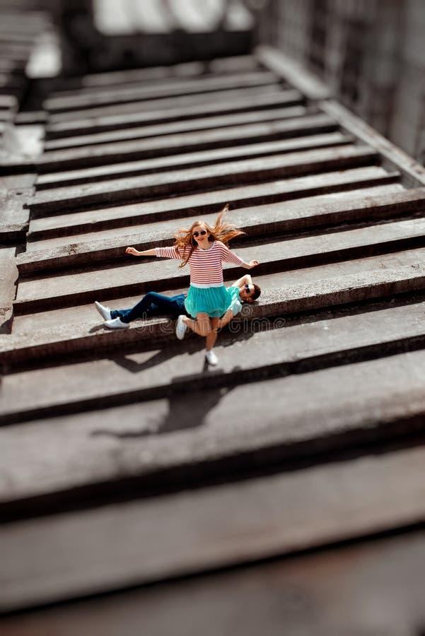 Glimlachend meisje die over de man op het grijze dak van flat springen stock fotografie