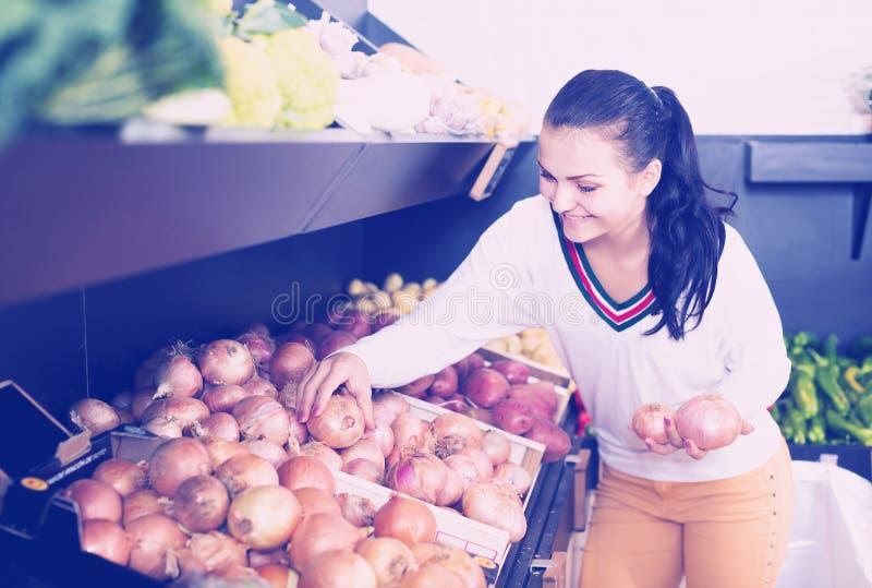 Glimlachend meisje die over uien beslissen stock afbeeldingen