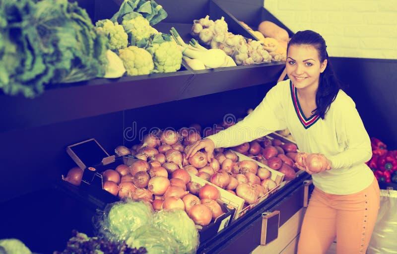 Glimlachend meisje die over uien beslissen stock fotografie