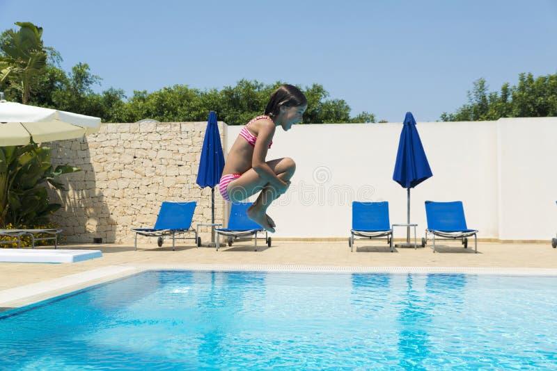 Glimlachend meisje die in pomp in een openluchtpool springen stock foto's