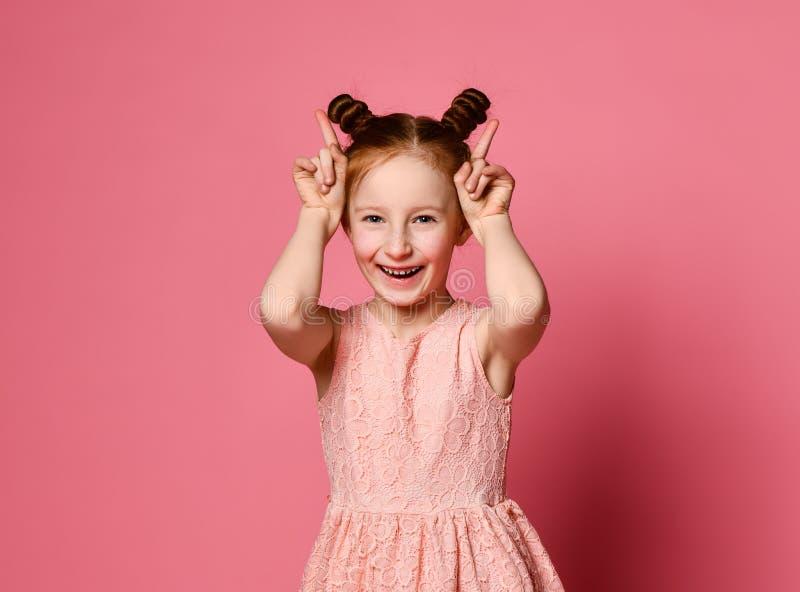 Glimlachend meisje die pret en het maken van hoornen door haar handen hebben stock foto's