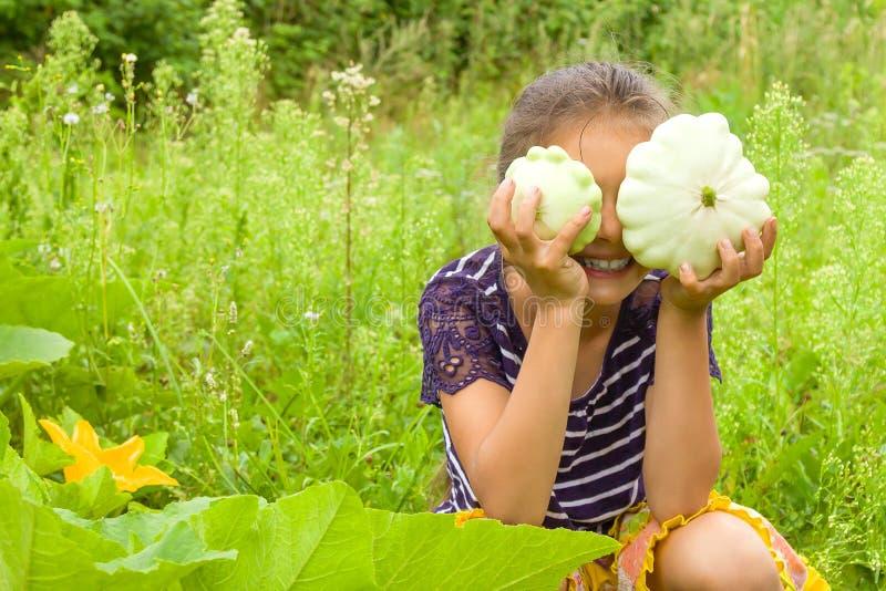 Glimlachend meisje die pret hebben en verse pompoenen in een tuin oogsten Zij verbergt haar ogen achter twee pompoenen royalty-vrije stock afbeelding
