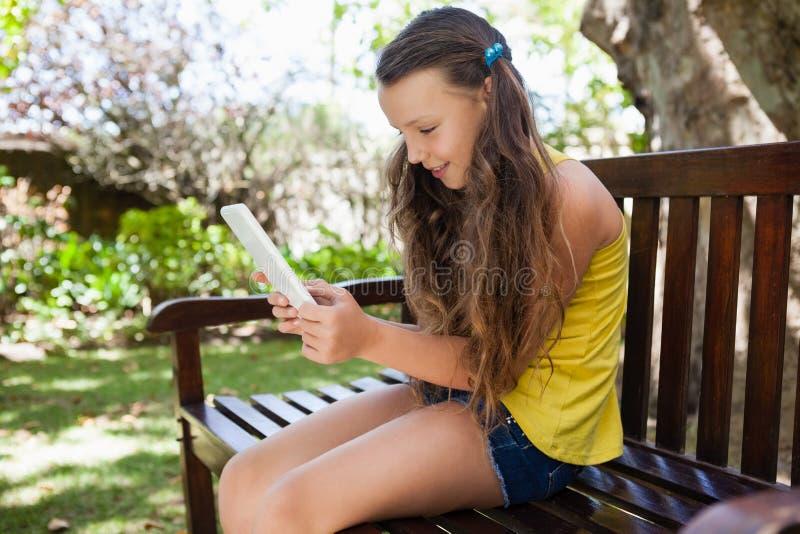 Glimlachend meisje die smartphone gebruiken terwijl het zitten op houten bank stock foto