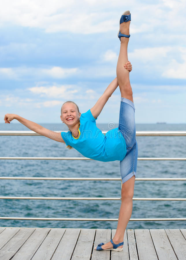 Glimlachend meisje die uitrekkende oefening maken door het overzees royalty-vrije stock foto's