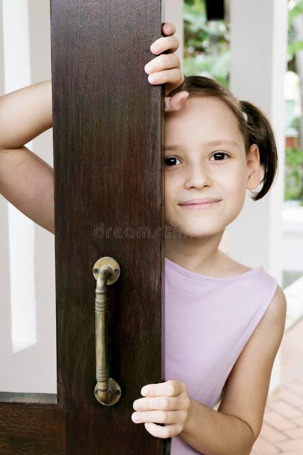 Glimlachend meisje die in violette kleding uit open deur in Skandinavisch stijlhuis kijken royalty-vrije stock foto's
