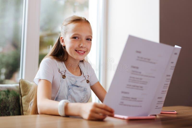 Glimlachend meisje die vrolijk terwijl het rusten met ouders in restaurant voelen stock afbeeldingen