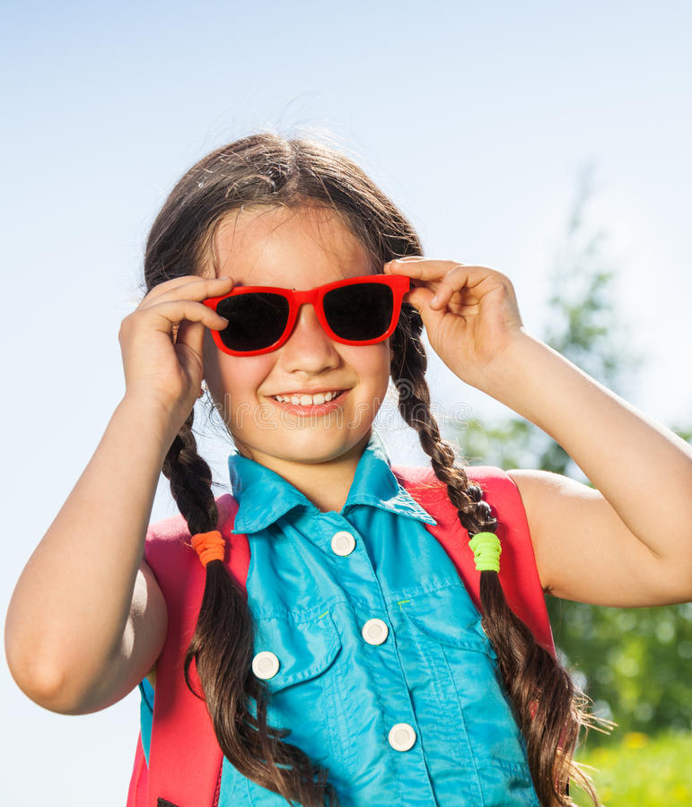 Glimlachend meisje die zonnebril met twee vlechten dragen royalty-vrije stock fotografie