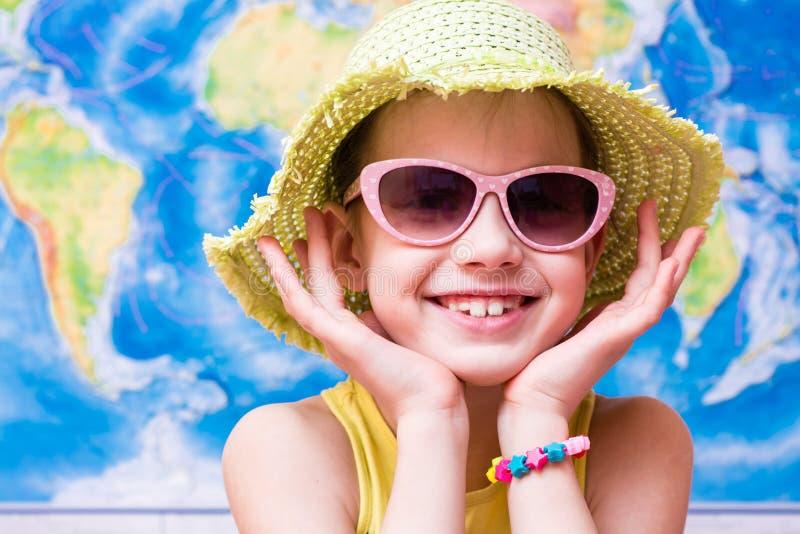 Glimlachend meisje in een hoed en zonnebril op de achtergrond van de wereldkaart stock fotografie