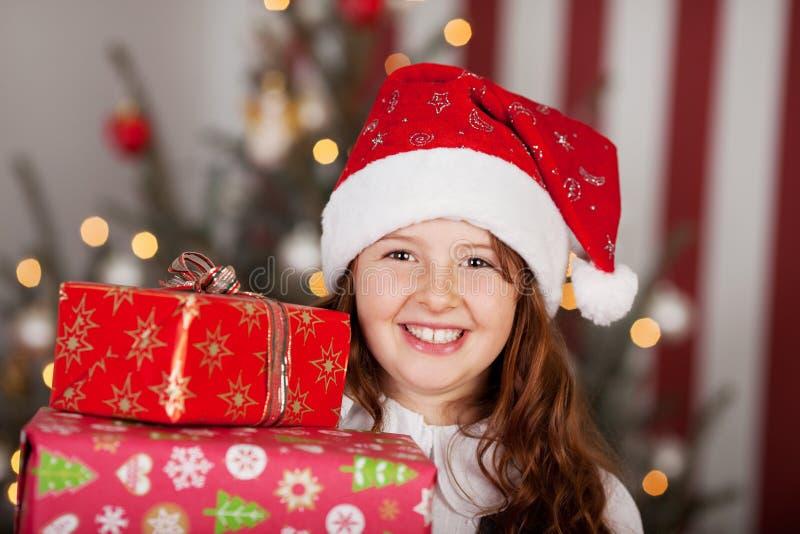Glimlachend meisje in een Kerstmanhoed met haar giften stock foto's