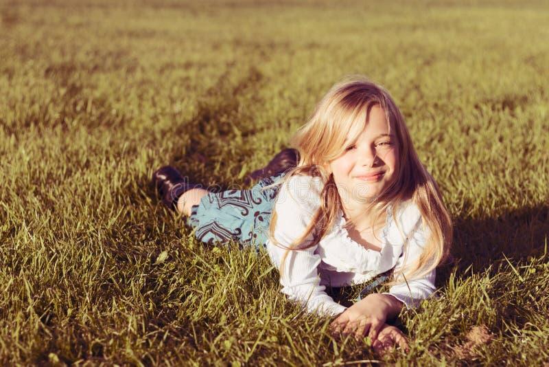 Glimlachend meisje in gras royalty-vrije stock afbeeldingen
