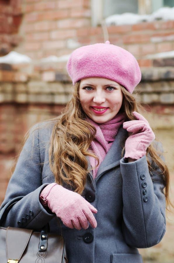 Glimlachend meisje in grijze laag en roze baret royalty-vrije stock fotografie