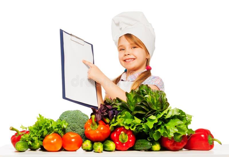 Glimlachend meisje in kok eenvormig met het winkelen lijst stock afbeeldingen