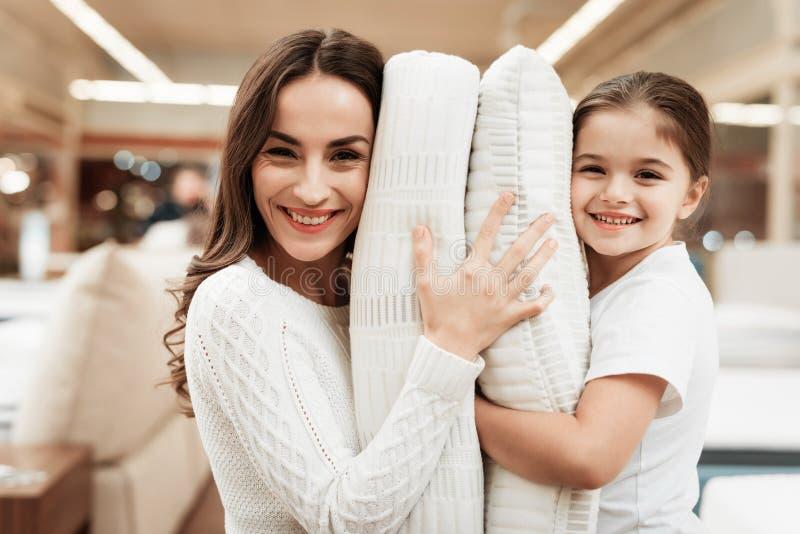 Glimlachend meisje met de mooie hoofdkussens van moederomhelzingen in opslag van orthopedische matrassen royalty-vrije stock foto's