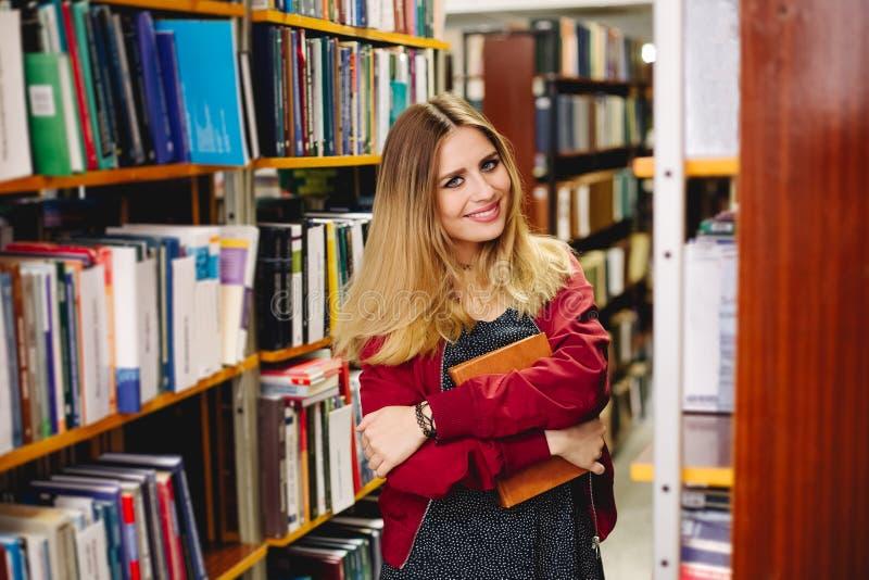 Glimlachend meisje met een boek in universitaire bibliotheek Het concept van het onderwijs stock afbeeldingen