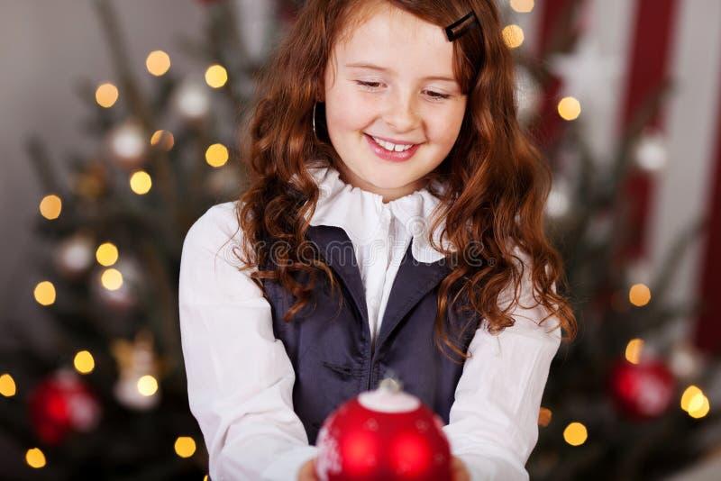 Glimlachend meisje met een Kerstmisbal stock afbeelding