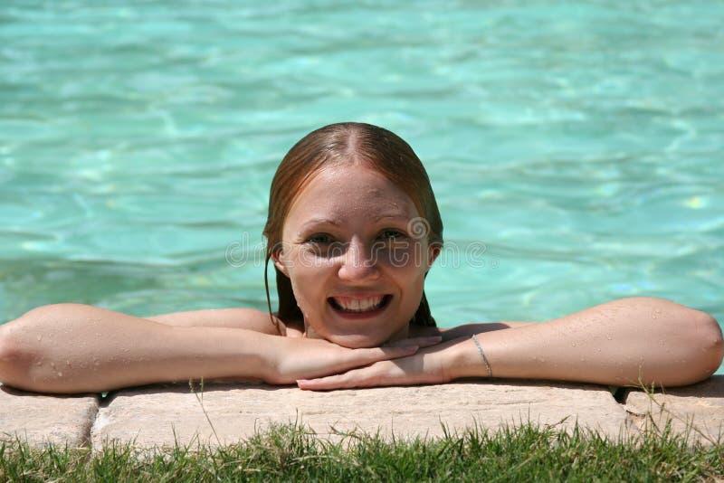 Glimlachend meisje met handen het uitgestrekte genieten die dichtbij zwembad zonnebaden stock afbeeldingen
