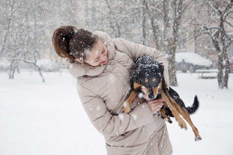Glimlachend meisje met hond in de wintersneeuw stock afbeelding