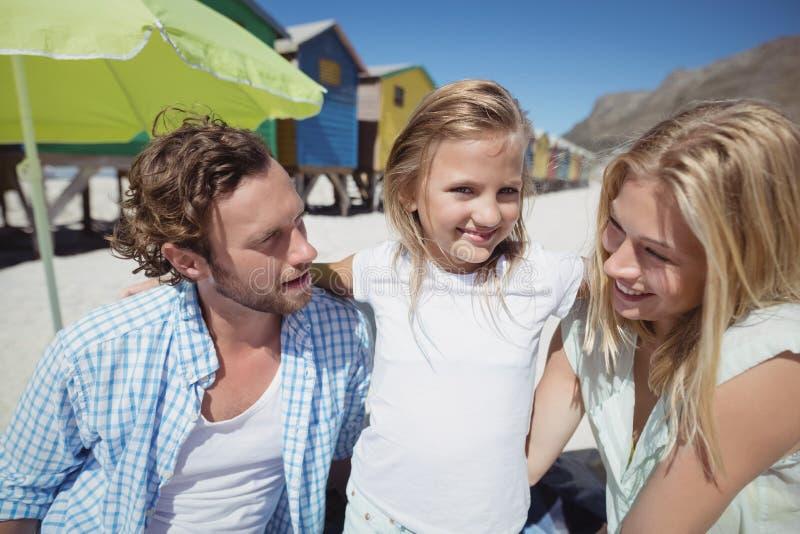 Glimlachend meisje met ouders bij strand royalty-vrije stock afbeelding