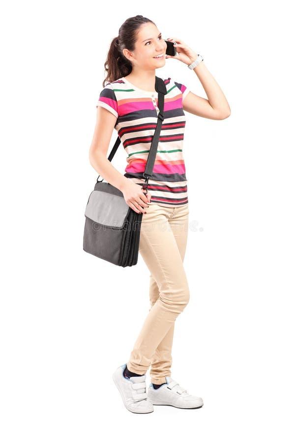 Glimlachend meisje met schouderzak die op een telefoon spreekt stock foto