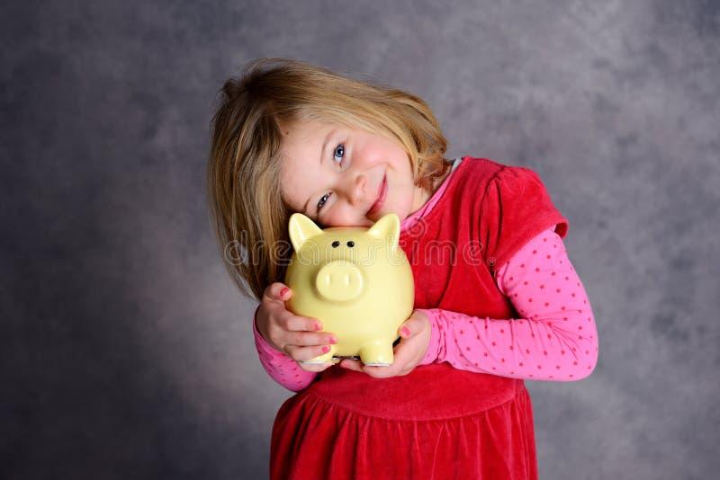 Glimlachend meisje met spaarvarken stock afbeeldingen