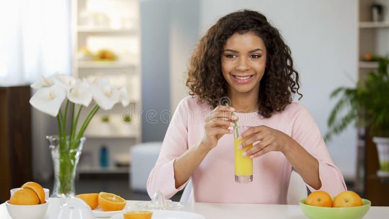 Glimlachend meisje met vers jus d'orangeglas, organische voeding, gezondheidszorggewoonte stock afbeeldingen