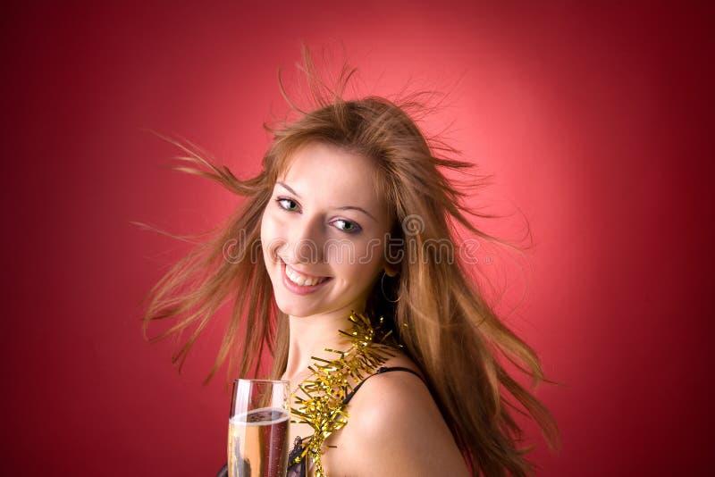 Glimlachend meisje met vliegend haar en champagneglas stock foto's